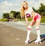 摆在桃红色短裤的葡萄酒溜冰鞋和白色T恤杉的美丽的性感的白肤金发的腿长的女孩在一个温暖的夏天晚上 Adju 库存照片