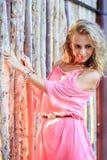 摆在桃红色礼服的白肤金发的妇女 免版税图库摄影