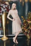摆在桃红色礼服的美丽的白肤金发的妇女 免版税库存照片