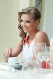 摆在桌上的快乐的可爱的妇女 免版税库存照片