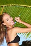 摆在棕榈叶的比基尼泳装的愉快的妇女 免版税库存照片
