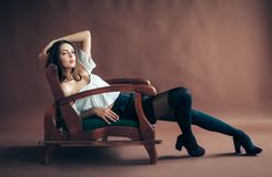 摆在棕色背景的沙发的美丽的少妇 Fashio 库存图片
