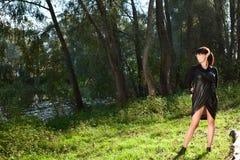 摆在森林沼地的黑礼服的女孩  免版税库存图片