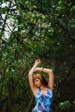 摆在森林里的蓝色礼服的白种人女孩在夏天 库存图片
