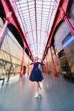 摆在楼梯的蓝色长的飞行礼服的端庄的妇女反对老城市大厦 库存照片