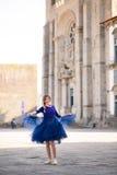 摆在楼梯的蓝色长的飞行礼服的年轻端庄的妇女反对老城市大厦 库存图片