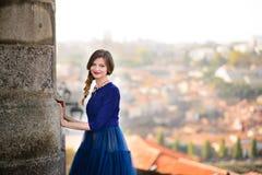 摆在楼梯的蓝色长的飞行礼服的年轻端庄的妇女反对老城市大厦 免版税库存图片