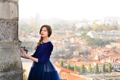 摆在楼梯的蓝色长的飞行礼服的年轻端庄的妇女反对老城市大厦 库存照片