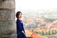 摆在楼梯的蓝色长的飞行礼服的年轻端庄的妇女反对老城市大厦 免版税图库摄影