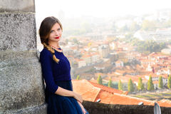 摆在楼梯的蓝色长的飞行礼服的年轻端庄的妇女反对老城市大厦 免版税库存照片