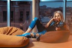 摆在橙色长沙发的逗人喜爱的年轻白肤金发的妇女在大wi附近 免版税库存照片