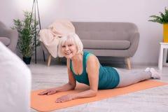 摆在欢乐的资深的妇女,当说谎在瑜伽席子时 库存照片