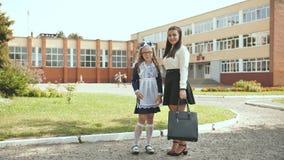 摆在欢乐衣裳的两个俄国女小学生姐妹在学期的初期的那天 股票录像