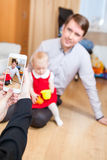 摆在母亲的父亲和小女儿,当拍与手机时的她照片 库存图片