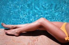 摆在比基尼泳装的性感的妇女在水池附近 免版税库存照片