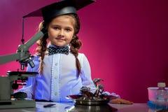 摆在毕业生帽子的逗人喜爱的女孩,在桃红色背景 免版税库存图片