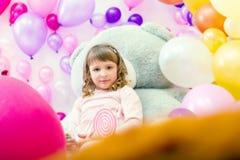 摆在气球背景的游戏室的逗人喜爱的女孩 图库摄影