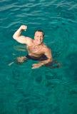 摆在水的愉快的笑的人 免版税库存照片
