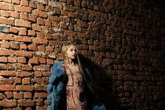 摆在水的背景女孩 在冬天夹克的小女孩姿势在砖墙上,时尚 与长的金发的儿童模型,发型和 免版税库存照片