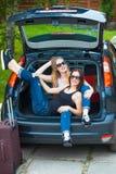 摆在汽车的两个女孩 免版税库存图片
