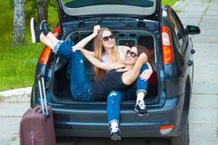 摆在汽车的两个女孩 图库摄影