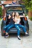 摆在汽车的两个女孩 免版税库存照片