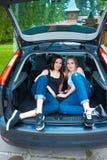 摆在汽车的两个女孩 库存图片