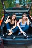 摆在汽车的两个女孩 库存照片