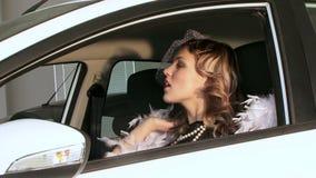 摆在汽车的减速火箭的样式的俏丽的妇女 股票录像