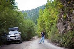 摆在汽车附近的少妇在森林里 免版税库存图片