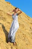 摆在沙子安排的美丽的妇女。 库存图片