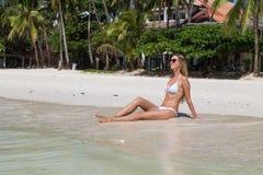 摆在沙滩的白色泳装的性感的被晒黑的女孩 美好的模型晒日光浴并且基于海洋岸 概念假期, 免版税库存图片