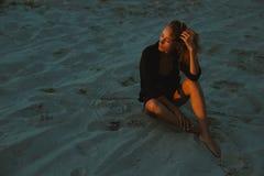 摆在沙漠沙子的性感的白肤金发的头发的少妇由红色落日光点燃了 库存照片
