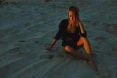 摆在沙漠沙子的性感的白肤金发的头发的少妇由红色落日光点燃了 免版税图库摄影