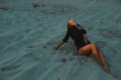摆在沙漠沙子的性感的白肤金发的头发的少妇由红色落日光点燃了 免版税库存照片