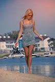 摆在河和去在与鞋子的海滩的女孩在手上 免版税库存图片