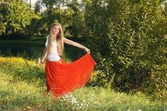 摆在河岸的树下的美丽的年轻白肤金发的妇女 免版税库存照片