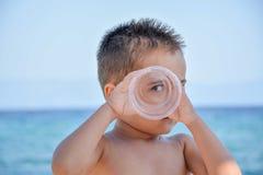 摆在海滩的一个逗人喜爱的男孩 免版税库存图片