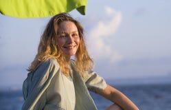 摆在海滩的年轻愉快的美丽和迷人的白肤金发的妇女在伞微笑下周道看无忧无虑的海 免版税库存图片