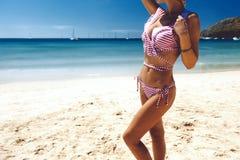 摆在海滩的式样佩带的时尚比基尼泳装 免版税库存图片