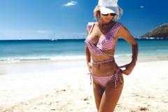 摆在海滩的式样佩带的时尚比基尼泳装 免版税图库摄影