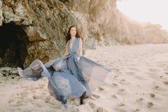 摆在海滩的蓝色婚礼礼服的新娘在日落或日出颜色 白肤金发的新娘礼服时装模特儿样式伞婚姻的白人妇女 免版税库存照片