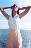 摆在海的美丽的时兴的女孩 免版税库存照片