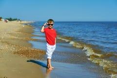 摆在海边的美丽的男孩在一个夏日 免版税库存图片