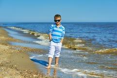 摆在海边的美丽的男孩在一个晴朗的夏日 免版税图库摄影