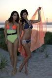 摆在海滩沙丘的两个时装模特儿穿在日落时间的性感的泳装 免版税库存图片