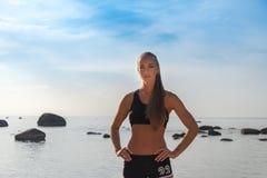 摆在海滩的体育妇女 免版税图库摄影