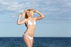 摆在海滩的愉快的健身妇女身体 免版税库存图片