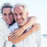 摆在海滩的有吸引力的已婚夫妇 图库摄影