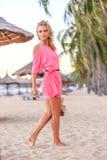 摆在海滩的桃红色礼服的白肤金发的妇女 免版税库存照片